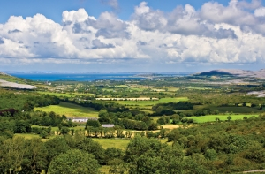 Landscape of County Clare, Ireland. Green fields in foreground and Galway Bay in the background. Beginings of the Burren can also be seen.